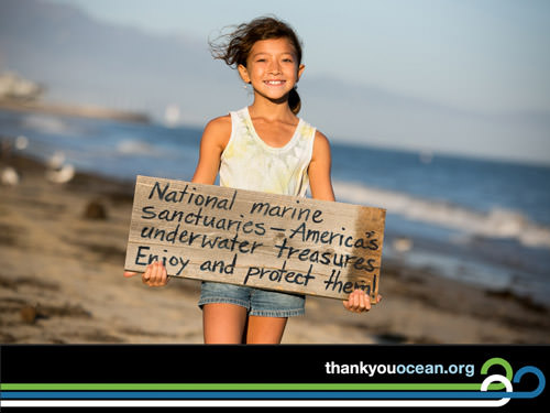 child holding sign with text saying: national marine sanctuaries - america's under water treasures, enjoy and protect