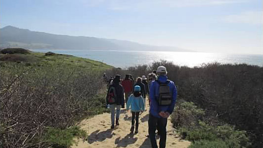 people walking a trail along the coast