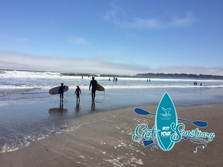 a family walking into the ocean with their surf boards in two