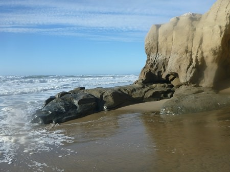 waves hitting the beach along a rocky shoreline